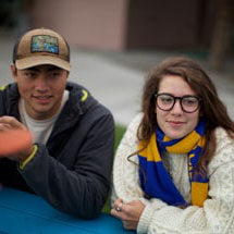 Male and Female Undergraduate students listening on a picnic table