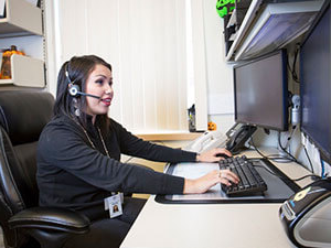 Woman looking at computer screen with headset on