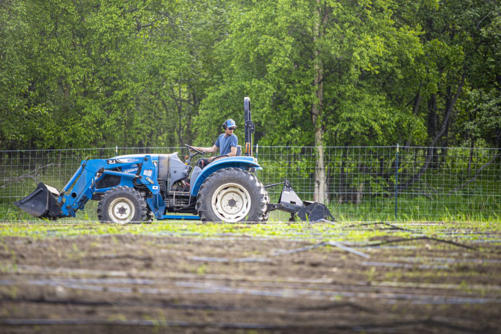 Student driving a tractor in a field